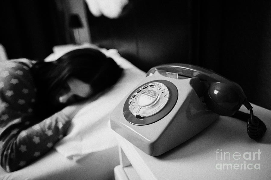 Table Photograph - Old Fashioned Gpo Bt Phone On Bedside Table Of Early Twenties Woman In Bed In A Bedroom by Joe Fox