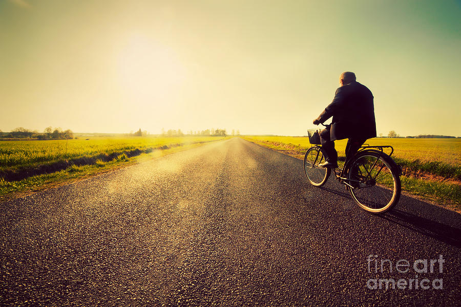 Road Photograph - Old Man Riding A Bike To Sunny Sunset Sky by Michal Bednarek