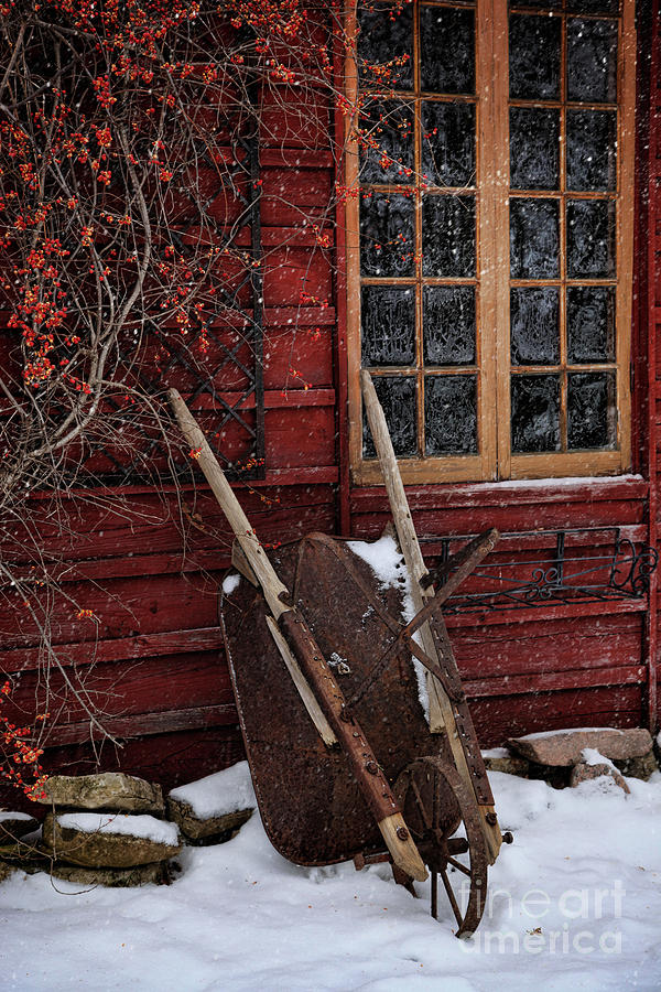 Atmosphere Photograph - Old wheelbarrow leaning against barn in winter by Sandra Cunningham