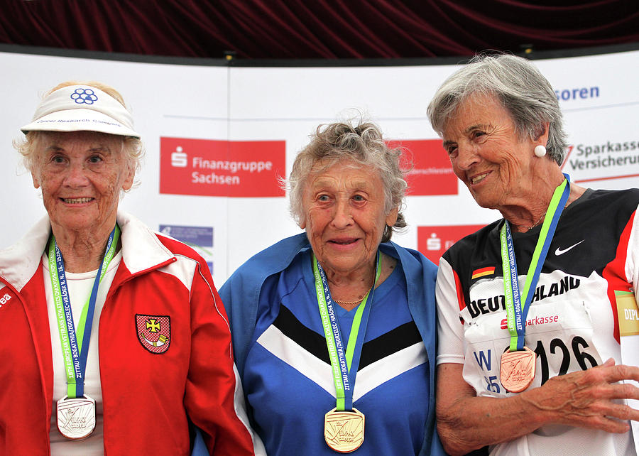 Female Photograph - Older Female Athletes On Medals Rostrum by Alex Rotas