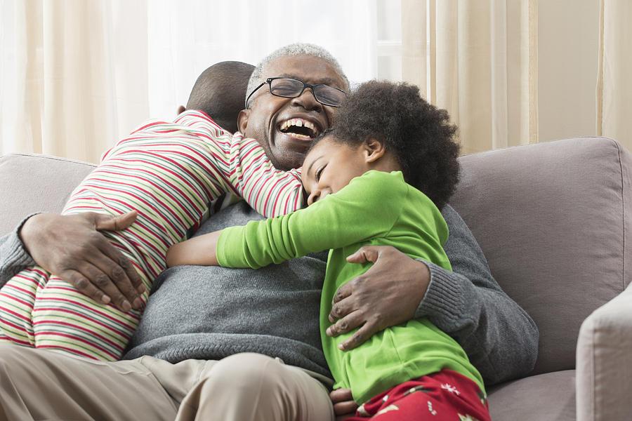 Older man hugging grandchildren on sofa Photograph by Jose Luis Pelaez Inc