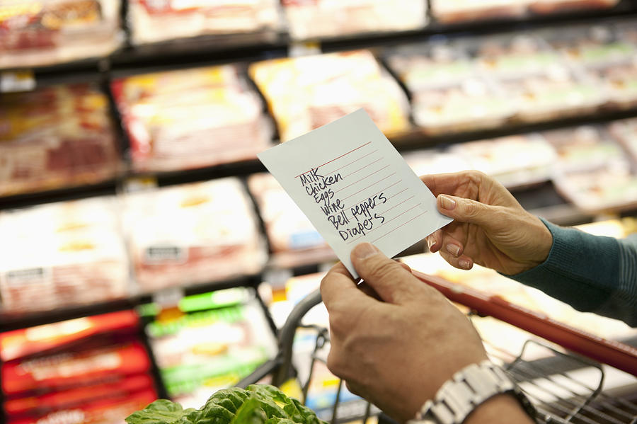 Older woman reading grocery list in supermarket Photograph by Robert Nicholas