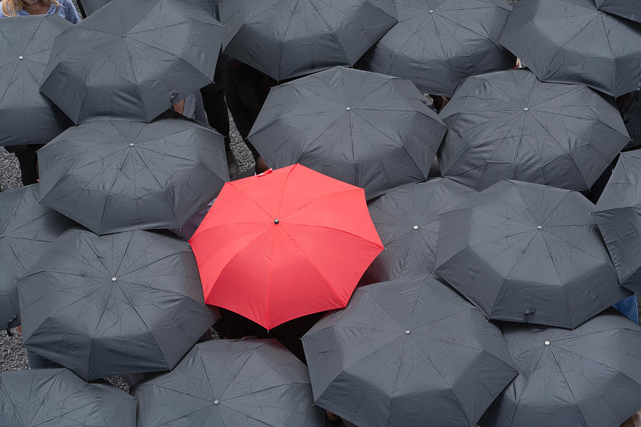 One red umbrella at center of multiple black umbrellas Photograph by Martin Barraud