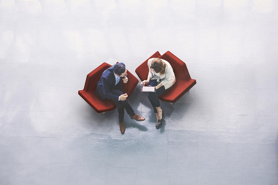 Overhead view of two business persons in the lobby Photograph by Piranka