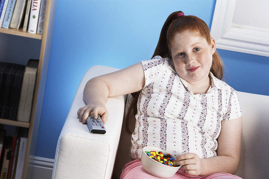 Overweight Child Eating Junk Food Photograph by Moodboard