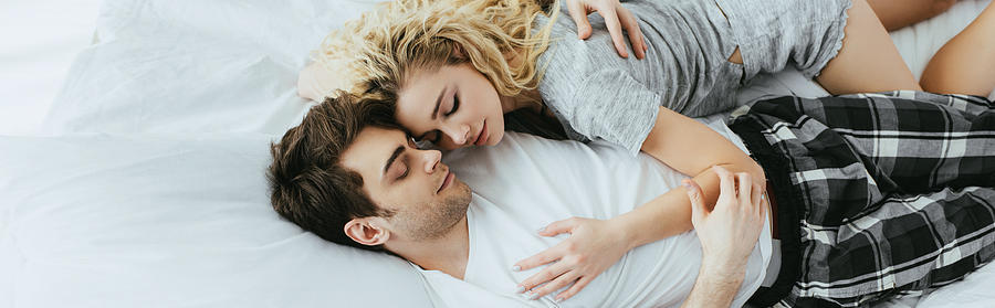 Panoramic Shot Of Happy Couple Hugging While Lying On Bed Photograph by LightFieldStudios