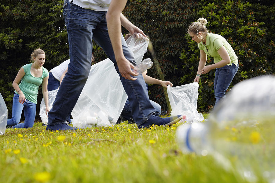People cleaning up litter on grass Photograph by Photo_Concepts