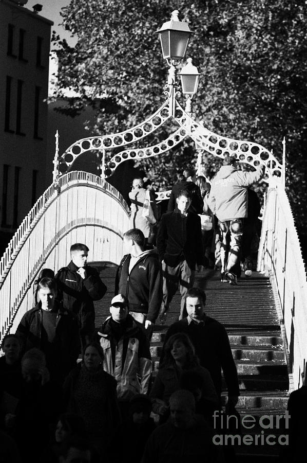 Dublin Photograph - People Crossing The Hapenny Ha Penny Bridge Over The River Liffey In Dublin At A Busy Time Vertical by Joe Fox