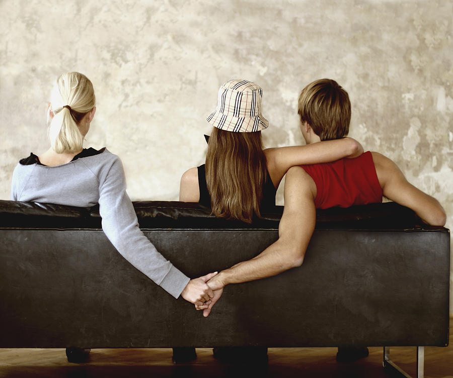 People Holding Hands on Sofa Photograph by Hannes Hepp