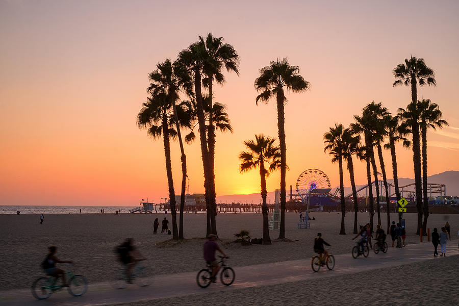 People ride bikes and walk along the beach at sunset in Santa Monica, California. Photograph by Brian Eden