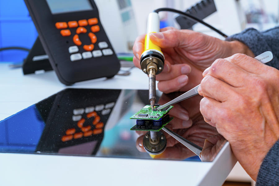 Male Photograph - Person Soldering An Electronic Component by Wladimir Bulgar/science Photo Library
