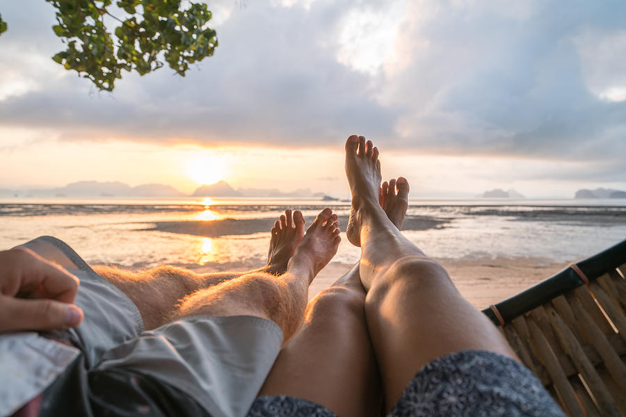 Personal perspective of couple relaxing on hammock, feet view Photograph by Swissmediavision