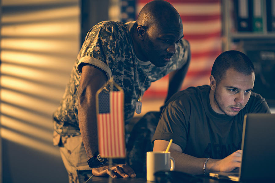 Photo of two young american soldiers looking at laptop Photograph by Geber86