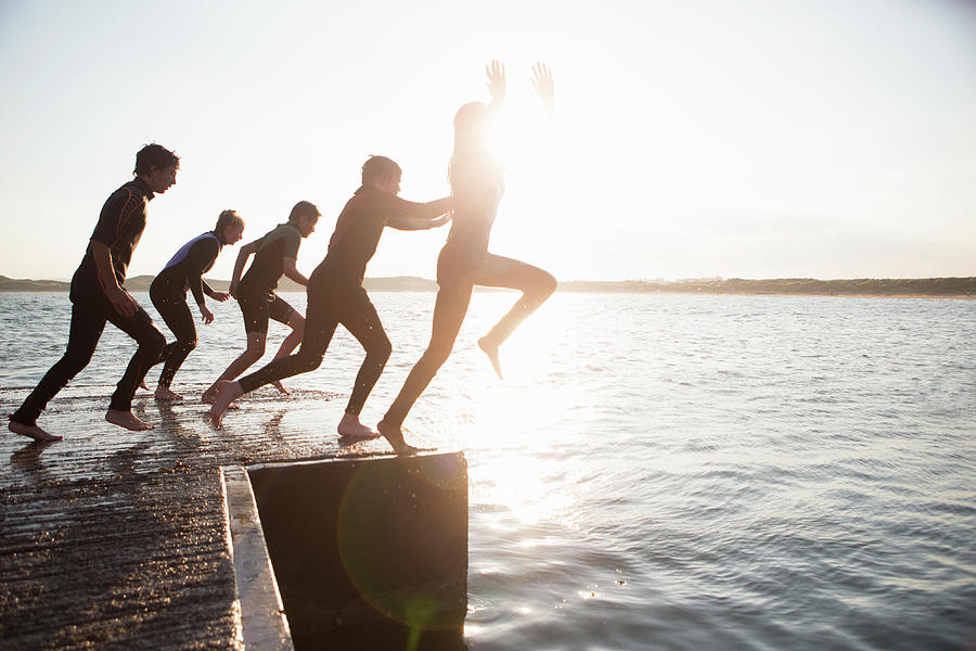 Pier Jumping Photograph by Solstock