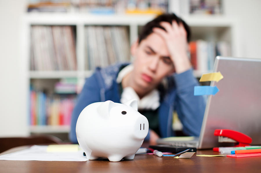 Piggy bank with young man worrying in background Photograph by Alys Tomlinson