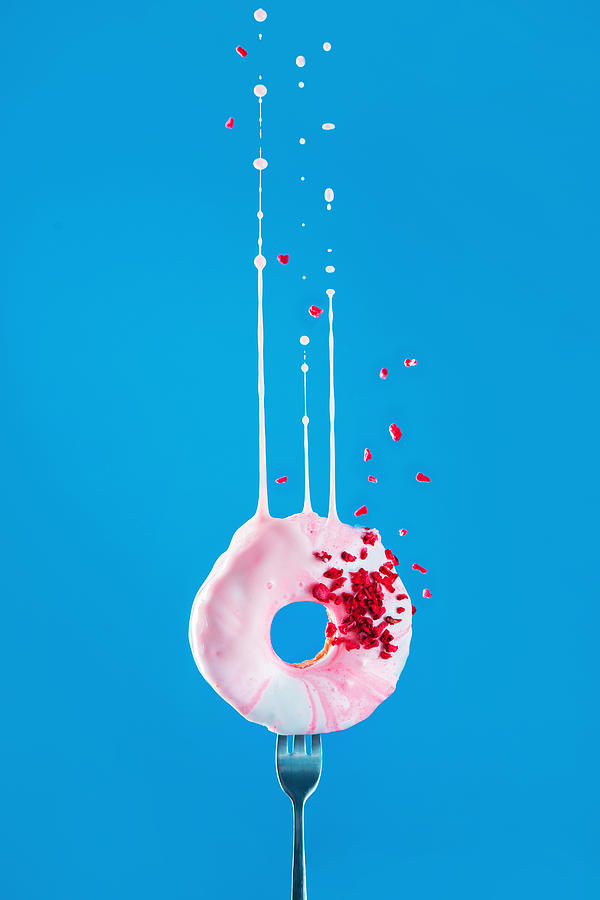 Pink donut with freeze-dried raspberry and a dymanic splash of pink glazing on a vibrant blue background, Flying food concept with copy space. Photograph by Dina Belenko Photography
