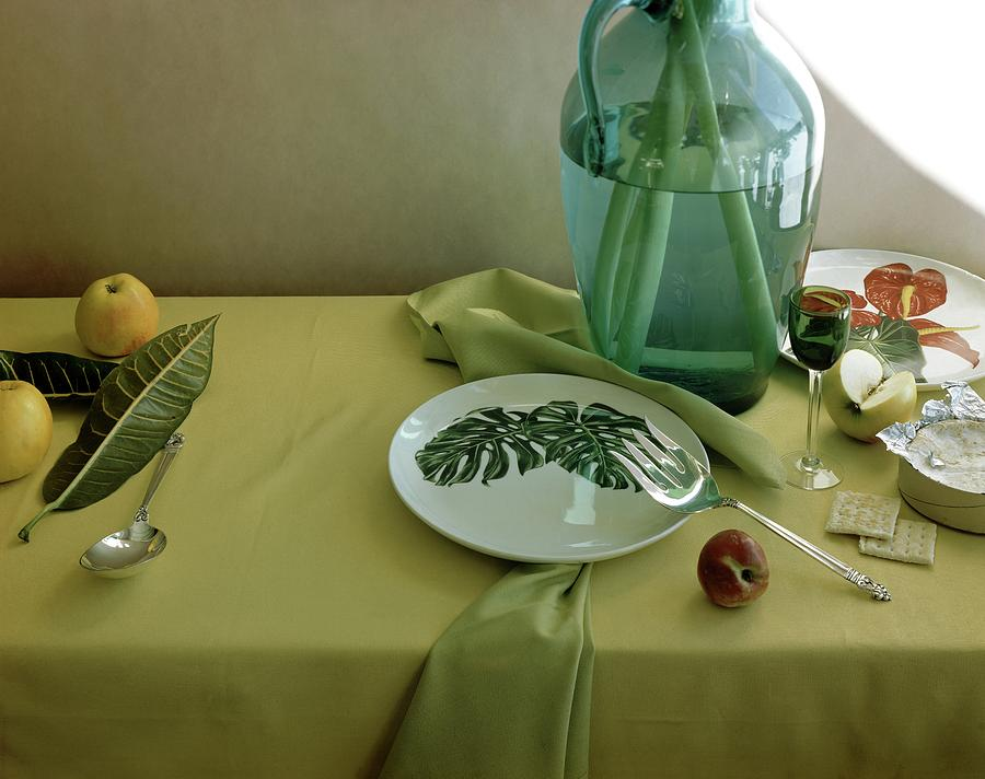 Plates, Apples And A Vase On A Green Tablecloth Photograph by Horst P. Horst