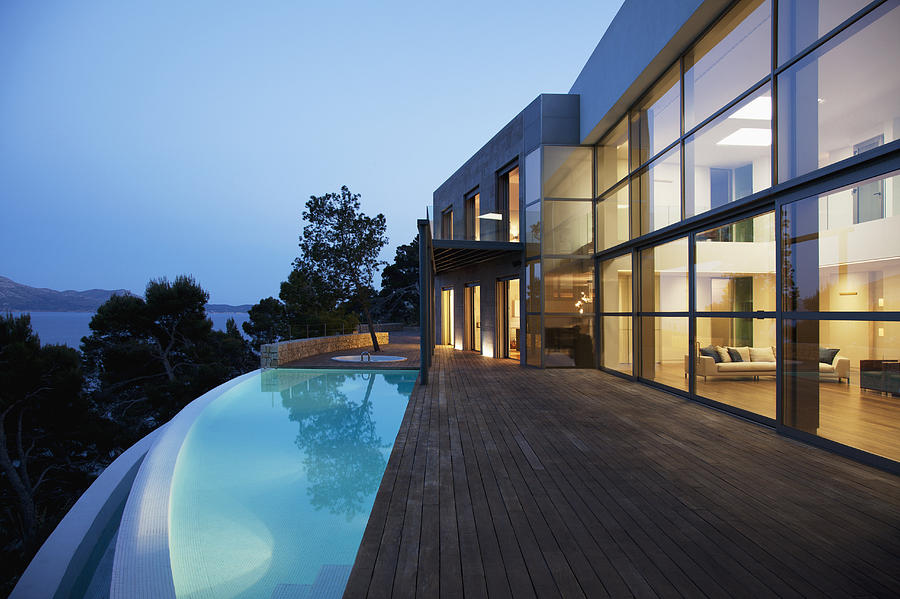 Pool outside modern house at twilight Photograph by Martin Barraud