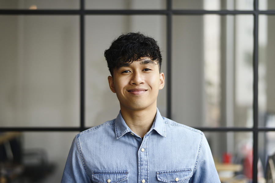 Portrait of a young Malay man in a modern office Photograph by Carlina Teteris
