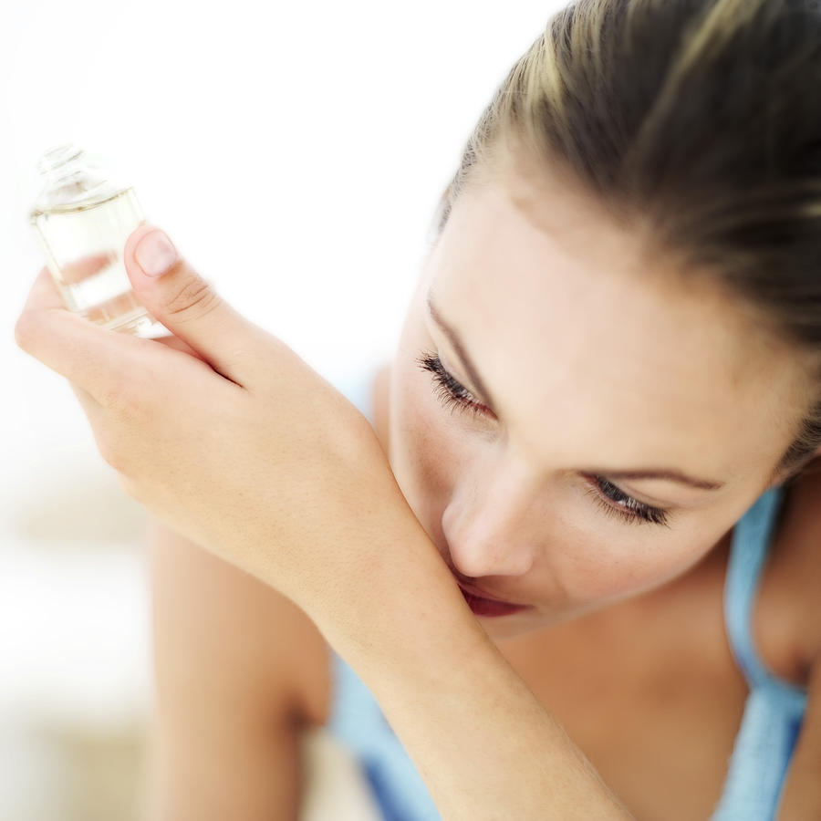 Portrait Of A Young Woman Smelling Perfume On Her Wrist Photograph by Stockbyte