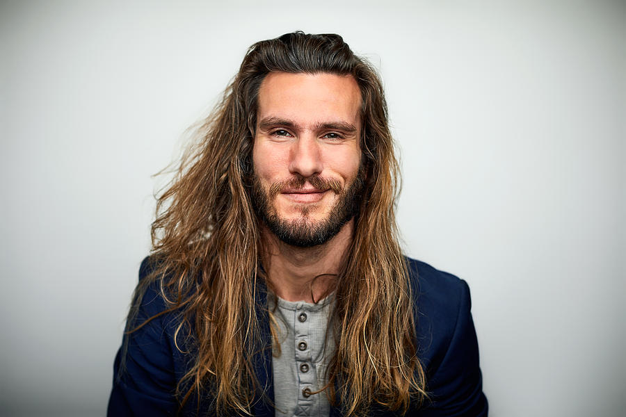 Portrait of confident man with long hair Photograph by Morsa Images