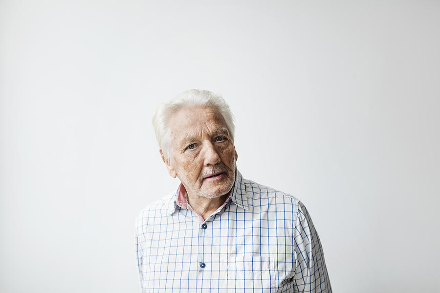 Portrait of confident senior man standing against white background Photograph by Maskot