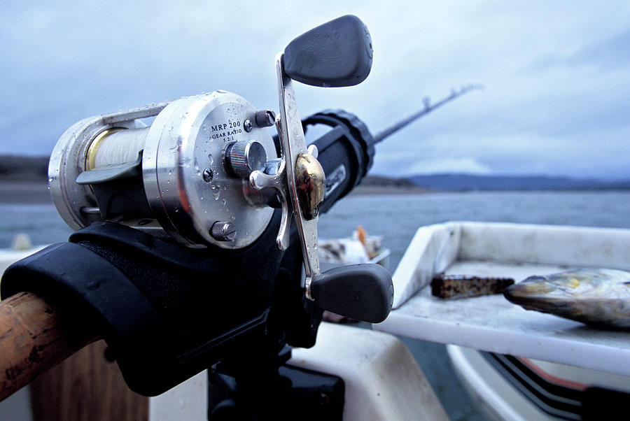 Angling Photograph - Portrait  Of Fishing Reel On Boat While by Justin Bailie