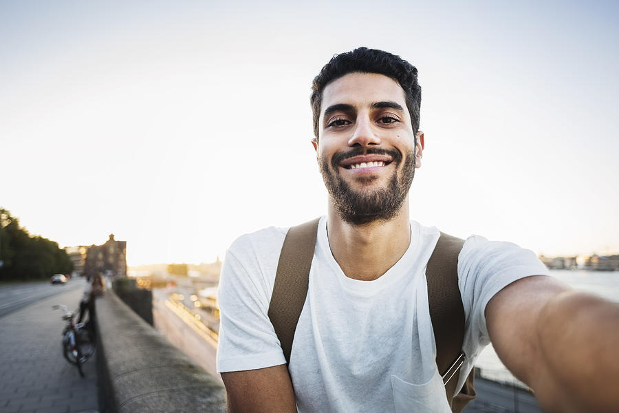 Portrait of happy male tourist sitting on retaining wall of bridge Photograph by Maskot