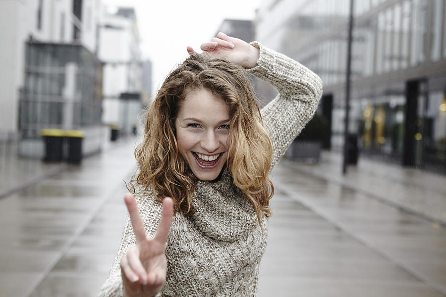 Portrait Of Happy Young Woman Showing Victory Sign Photograph by Westend61