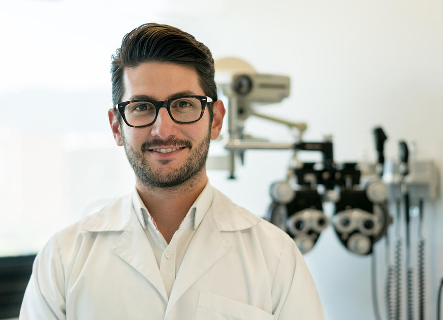 Portrait Of Male Opthalmologist Looking At Camera Smiling And A Phoropter  At The Background by Andresr