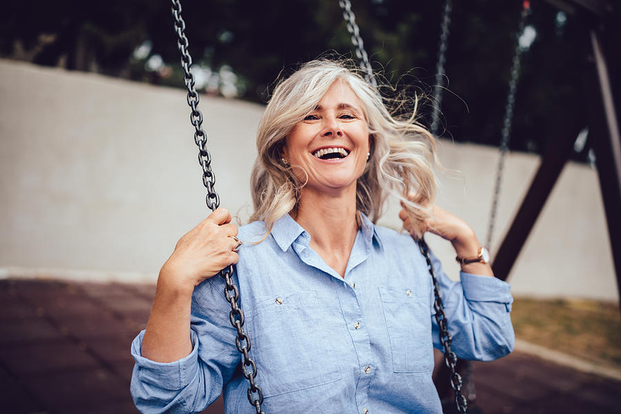 Portrait of mature woman with gray hair sitting on swing Photograph by Wundervisuals
