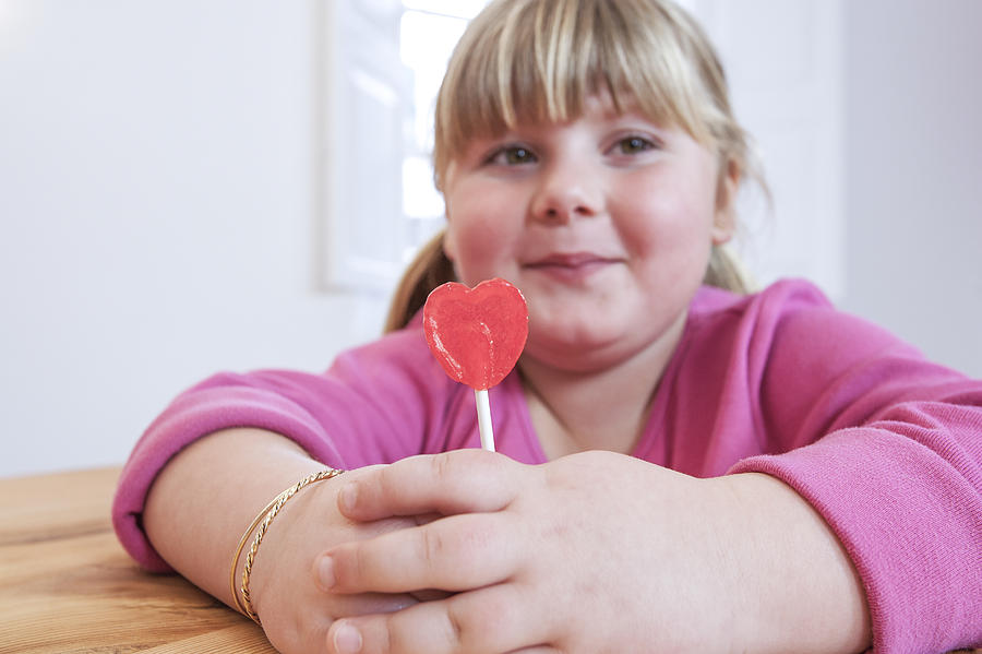 Portrait of overweight girl holding heart shape lollipop Photograph by Russ Rohde