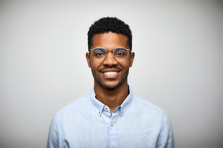 Portrait of smiling young man wearing eyeglasses Photograph by Morsa Images
