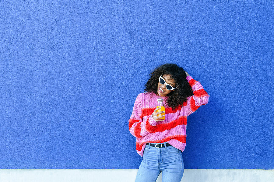 Portrait of smiling young woman with bottle of orange juice standing in front of blue wall Photograph by Westend61