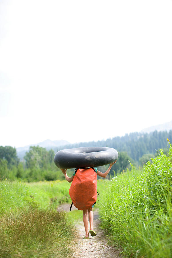 Anticipation Photograph - Pre Teen Girl Carrying An Inner Tube by Woods Wheatcroft