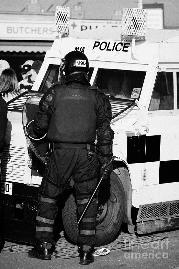 Northern Photograph - Psni Officer With Riot Gear And Baton In Front Of Land Rover On Crumlin Road At Ardoyne Shops Belfas by Joe Fox