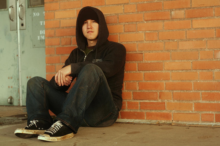 Punk And A Hoodie With Dirty Shoes Sitting By Brick Wall Photograph by Jordanchez