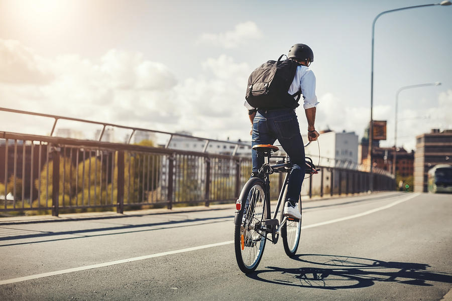 Rear view of businessman riding bicycle on bridge in city Photograph by Maskot