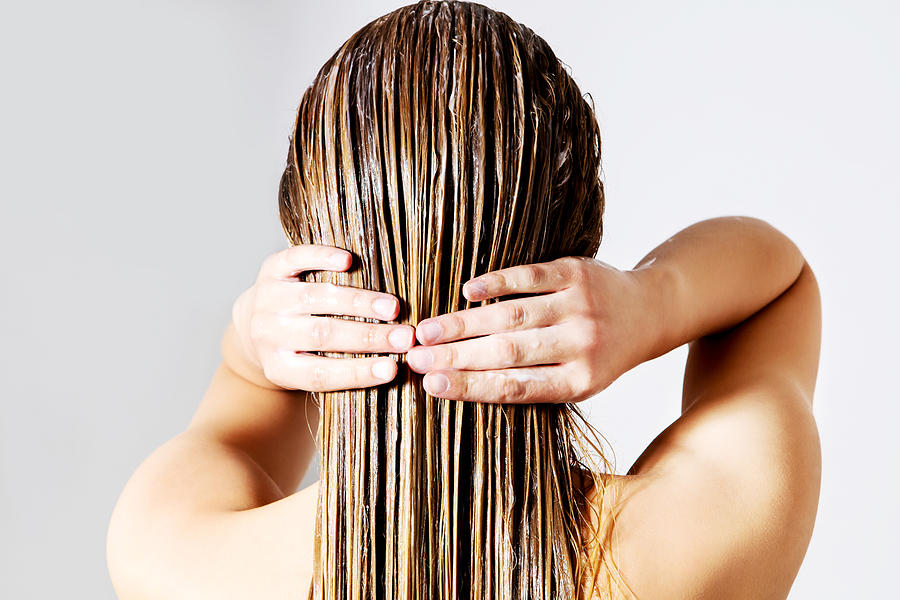 Rear View Of Woman Applying Conditioner On Hair Against White Background Photograph by Piotr Marcinski / EyeEm