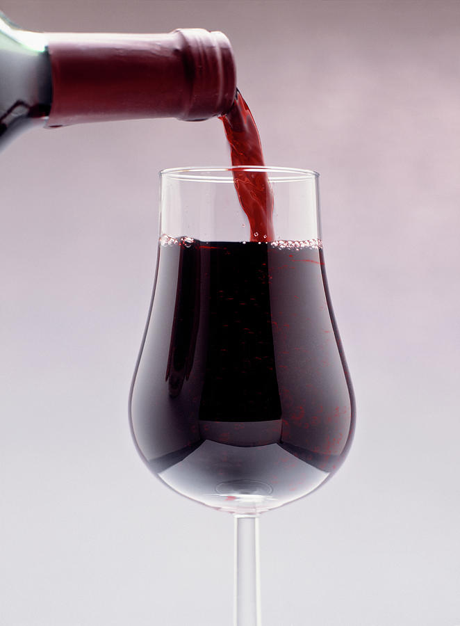 Vertical Photograph - Red Wine Bottle Pouring Into A Glass by Panoramic Images