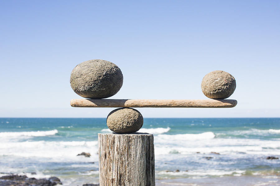 Rocks Balancing As Scale On Wooden Plank Photograph by Dimitri Otis