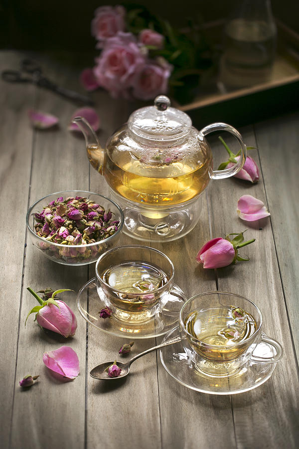 Rose tea in decorative cup on wooden table top. Photograph by Twomeows
