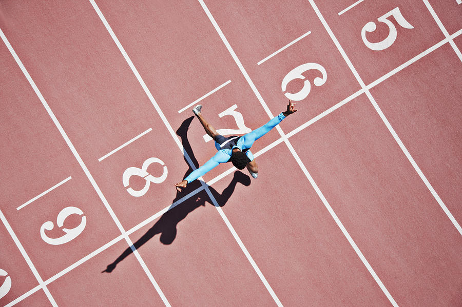 Runner crossing finishing line on track Photograph by Paul Bradbury