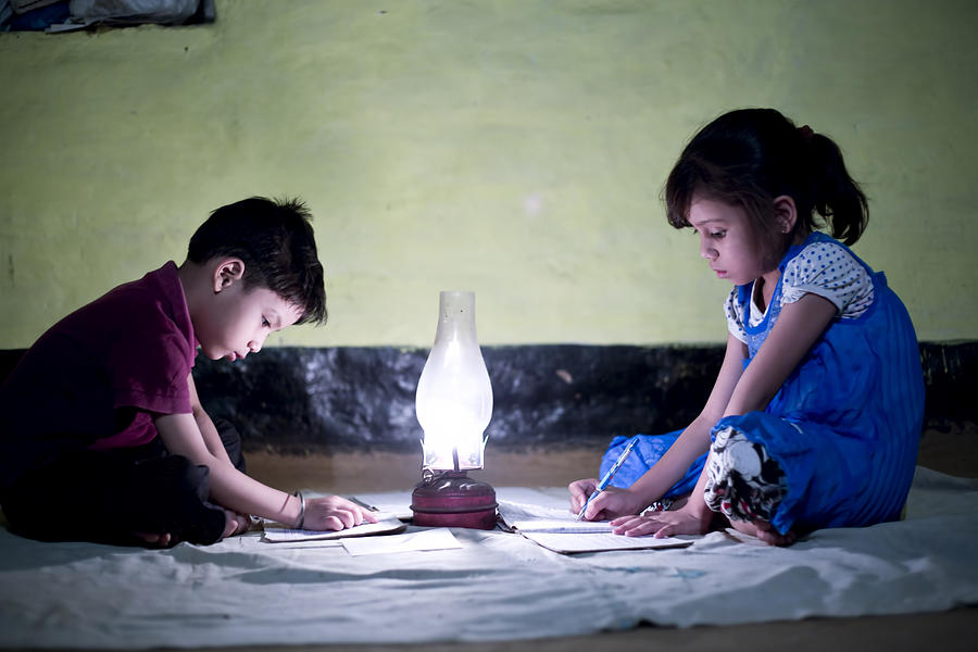 Rural girl and boy studying in lantern Photograph by Triloks