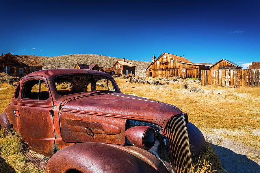 1800's Photograph - Rusted Car And Buildings, Bodie State by Russ Bishop