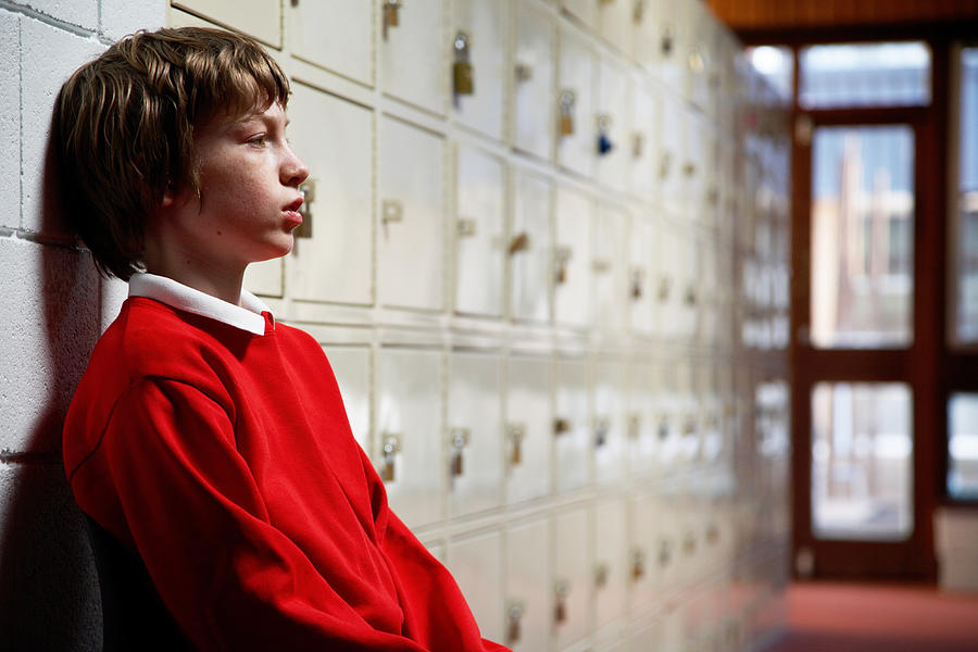 Schoolboy (11-13) sitting in corridor leaning head on wall, side view Photograph by Ableimages