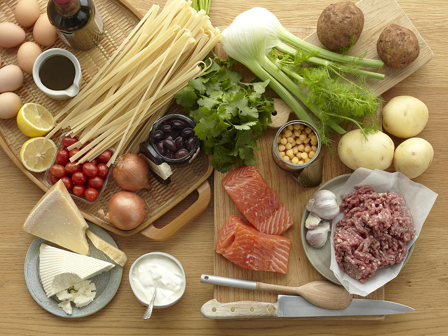 Selection of fresh raw foods with eggs, pasta, herbs, cheese, vegetables, salmon and minced pork Photograph by Brett Stevens