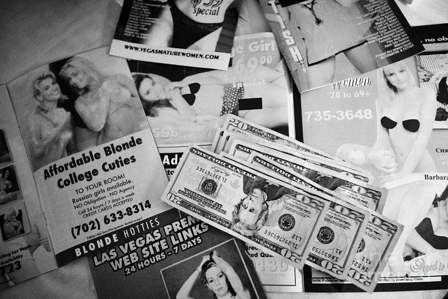 Advert Photograph - Selection Of Leaflets Advertising Girls Laid Out On A Hotel Bed With Us Dollars Cash In An Envelope  by Joe Fox