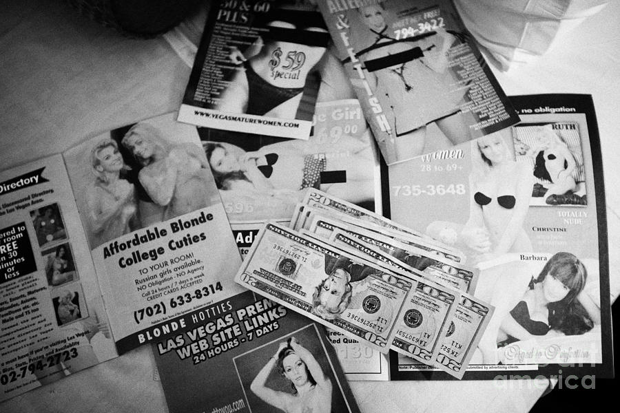 Advert Photograph - selection of leaflets advertising girls laid out on a hotel bed with us dollars cash in Las Vegas Ne by Joe Fox