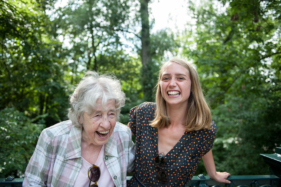 Senior (98) Lady And Young Woman Laughing In Park Photograph by Lucy Lambriex